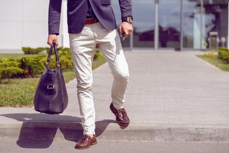 fashionably geklede zakenman loopt van kantoorgebouw met een tas en autosleutels in zijn hand.