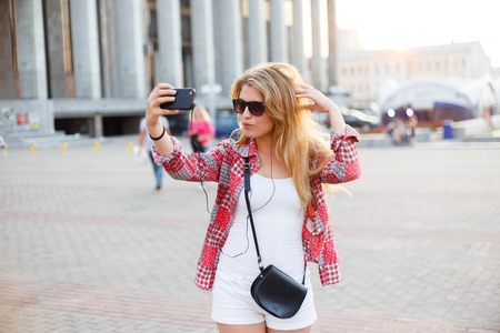 holydays: Young pretty woman taking a selfie at the square in the city. Summer holydays.