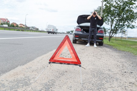 one lane road sign: A car with a breakdown alongside the road, man sets the warning triangle