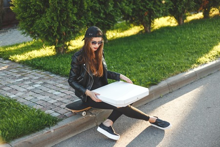 young woman - teenager with skateboard have a rest and eating pizza takeaway outdoor