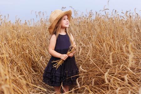 gelukkige jonge vrouw in zwarte jurk en zonnehoed genieten op graangewassengebied Stockfoto