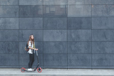 fasade: Joyful woman riding a kick scooter on modern fasade wall in background