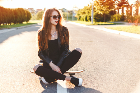 beautiful sexy girl with long legs in jeans short overalls sits on skateboard