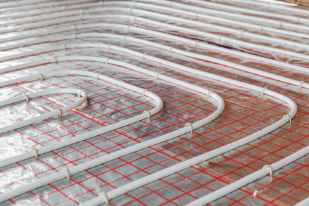 Underfloor heating installation. Close up on water floor heating system interior. plumbing pipes. Individual Heating.