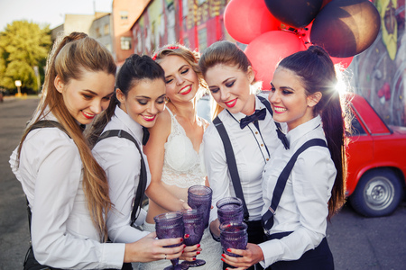 Beautiful happy girls celebrate a bachelorette party and drink champagne. Bridesmaids dresses in men's suits. The bride in a white sexy dress. Standard-Bild