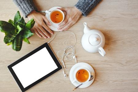 Meisje, zittend aan de tafel en groene thee drinkt. Tablet met lege ruimte en hoofdtelefoon ligt in de buurt.