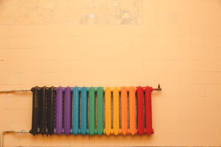 Old cast-iron radiator, painted in different colors on a blank wall. Copyspace above the radiator. 版權商用圖片