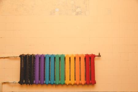 Oude gietijzeren radiator, geschilderd in verschillende kleuren op een blinde muur. Copyspace boven de radiator.