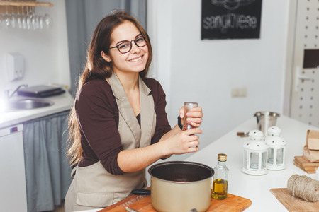 adds: Happy female adds salt or spices into soup pan at the kitchen Stock Photo
