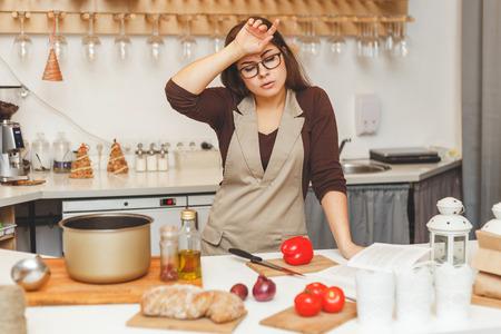 mooie jonge huisvrouw in de keuken is moe koken tomatensoep.