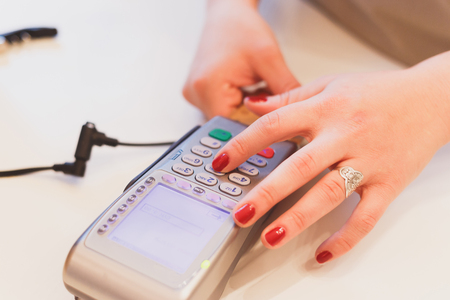 pin code: Closeup of girls hands entering the PIN code, paying for the purchase of banking magnetic card.