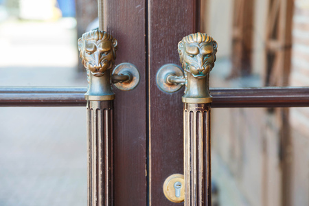 otras: old style wooden door with handles in the form of lions head.