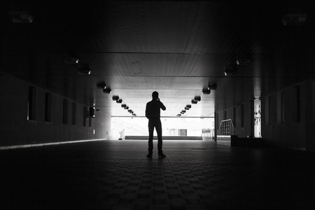 Dark silhouette of a man making an anonymous phone call.