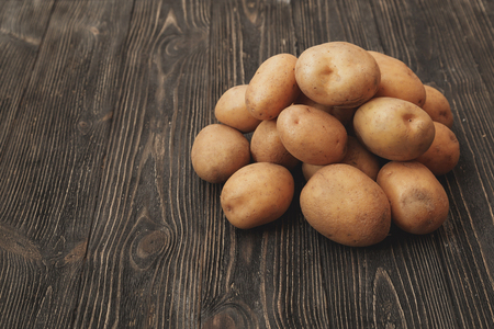 tuberous: Handful of Raw harvested potatoes on dark wooden background