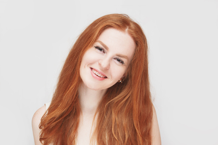 Smiling redhair girl wearing braces, cheerful portrait