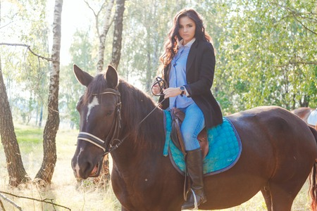 Beautiful sexy brunette wearing jeans, blouse and black jacket riding a horse at sunny summer day.