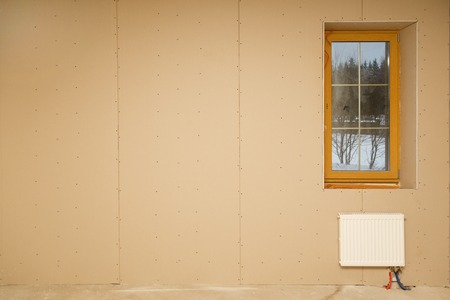 roughing: Heating radiator under window in the room without finishing during construction. Copy space on left part.