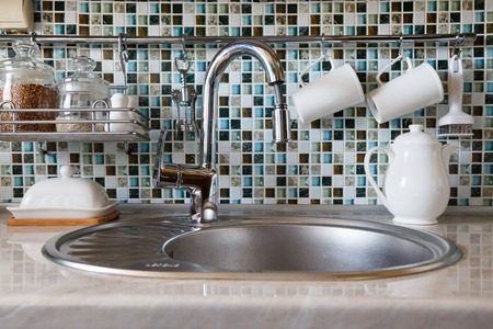 imbedded: Modern kitchenware and utensils including mugs, cups, tea pot and jars with cereal around tap and sink.