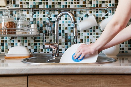 imbedded: A girl washes a white plate with a sponge in a modern kitchen. In the frame there are different kitchen utensils