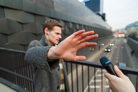 A young man is categorically against giving an interview to a journalist on the street. 版權商用圖片