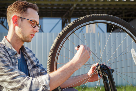 The mechanic man repair wheel of the bicycle. outdoor Stock Photo