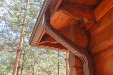 Roof gutter system on log house in forest Standard-Bild