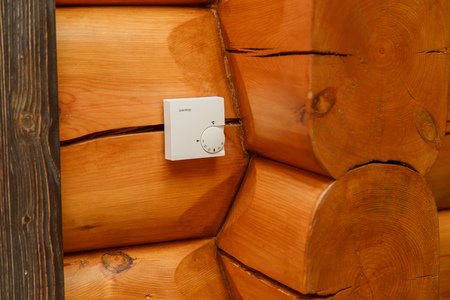 temperature controller: Room temperature controller for heating and cooling on a wall in a wooden house Stock Photo