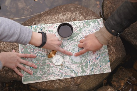 Scout tourists plan the route, orientate on the terrain on the map and the compass. View from above