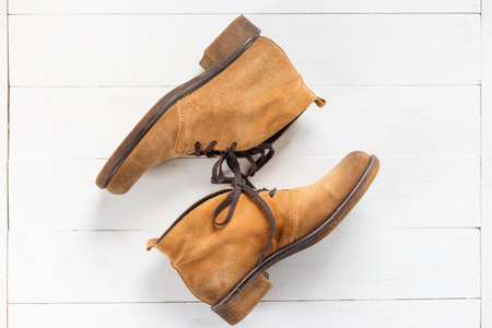 Pair of new nubuck boots on white wooden background. Top view Stock Photo