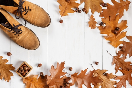 Suede ginger fashion shoes with yellow fallen oak leaves on white wooden background. Top view with copyspace Stock Photo