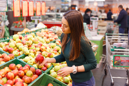 Young woman buy apples in farm food store