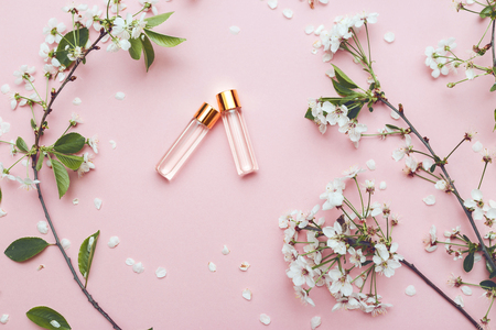 Two bottles of perfume with apricot blossom Imagens