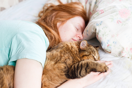 Young redhair woman sleeping with cat Stock Photo