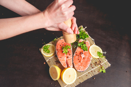 A woman sprinkles salmon with pepper from a pepper mill Stock Photo