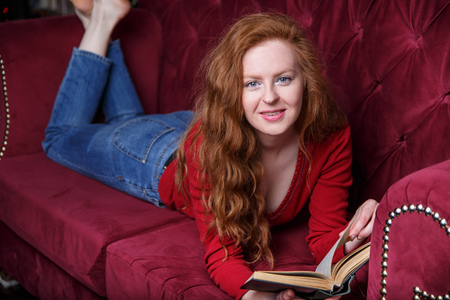 Rich young redhead woman reading a book on red velvet sofa