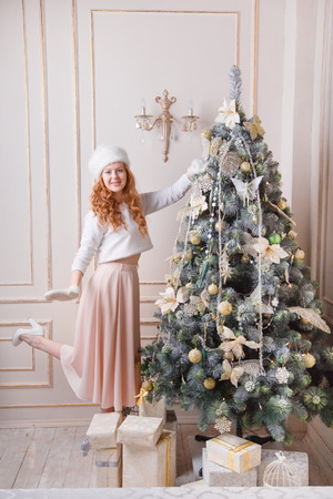 Redhead woman decorating a Christmas tree
