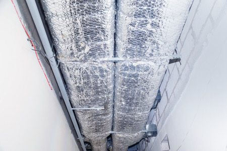 HVAC Duct Cleaning, Ventilation pipes in silver insulation material hanging from the ceiling inside new building Stock fotó