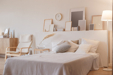 Bedroom interior with floor lamp and planty photoframes Stockfoto