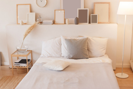 Bedroom with switched on floor lamp and photo frames. Banco de Imagens