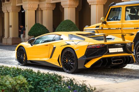 DUBAI, UAE - JANUARY 08, 2019: yellow luxury supercar Lamborghini Aventador Roadster and Gelandewagen.