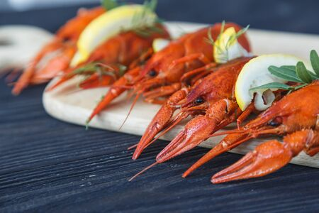 Close-up of boiled crawfish with lemon and herb