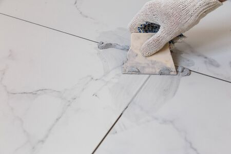 Grouting tiles seams with a rubber trowel