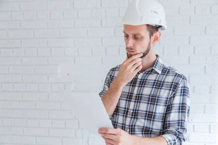 Pensive engineer in hard hat reading a document