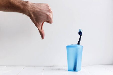 old used toothbrush and thumb down on white background.