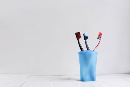 Family toothbrushes in blue cup on white wooden shelf.