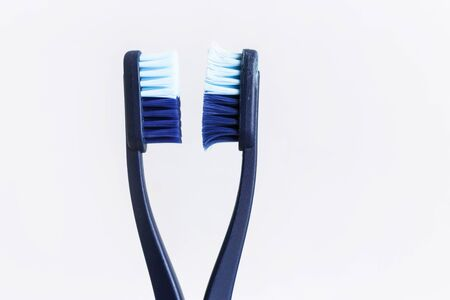 New and used blue color toothbrush in cup on white