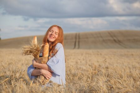Woman farmer or baker with baguettes in rye, wheat field Stockfoto