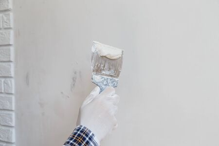 Worker in white gloves performs plastering of the walls of the room