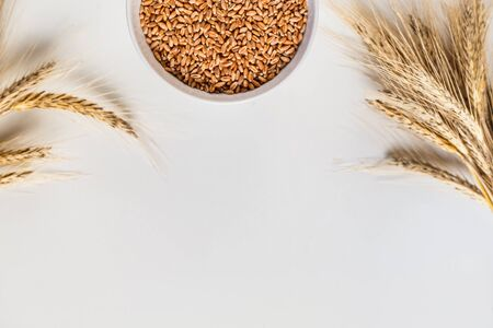 wheat ears and bowl of grains on white background, flat lay.