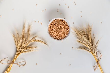 wheat ears and bowl of grains on a white background, flat lay